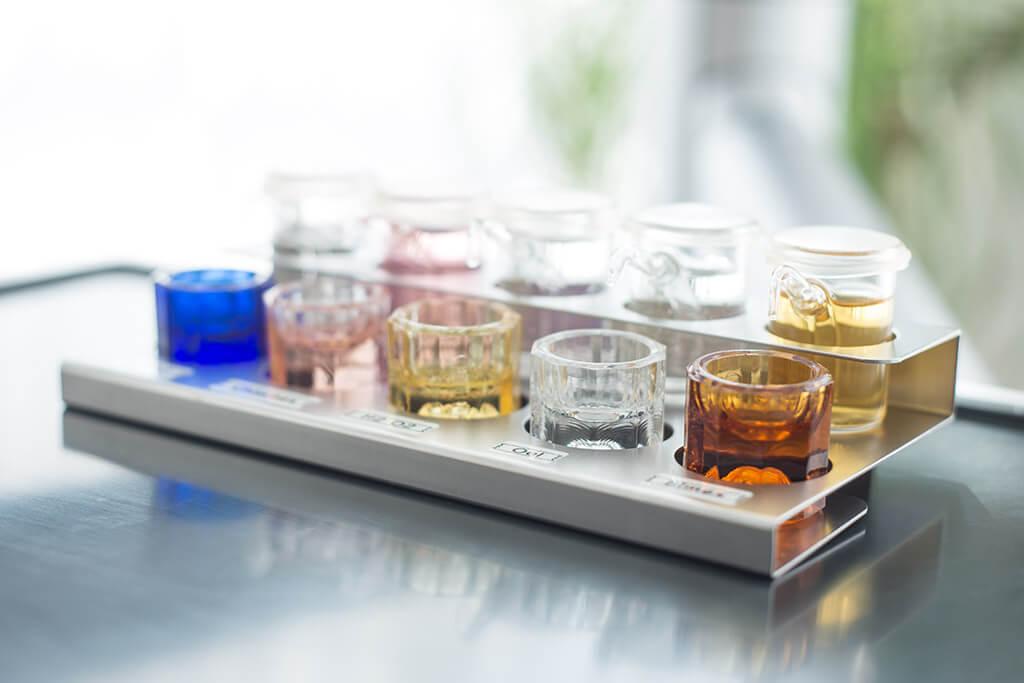 Zahnmedizinische Utensilien – Bunte Gläser und Flüssigkeiten.