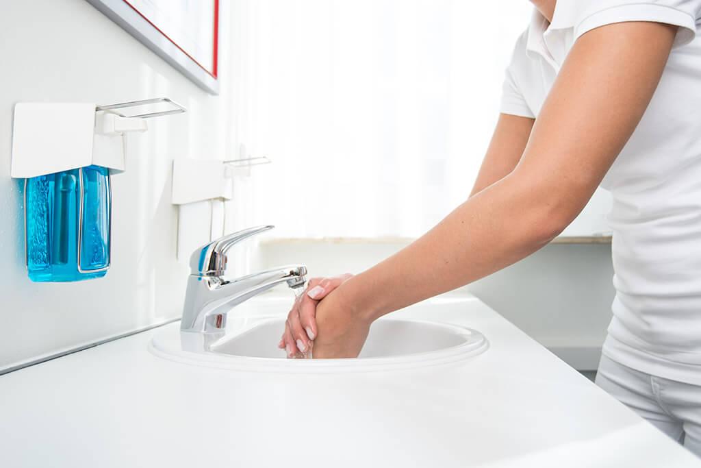 Hygiene – Mitarbeiterin beim Händewaschen und Desinfizieren.